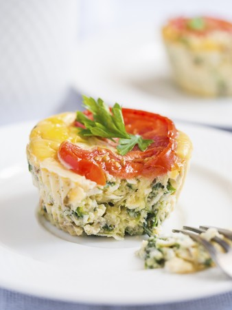 Breakfast egg muffins with spinach, zucchini and tomatoes, close up