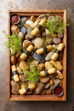 seaweeds: Spring rolls served on a wooden tray with stones (Asia)