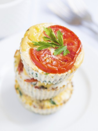 Breakfast egg muffins with spinach, zucchini and tomatoes arranged in a pile