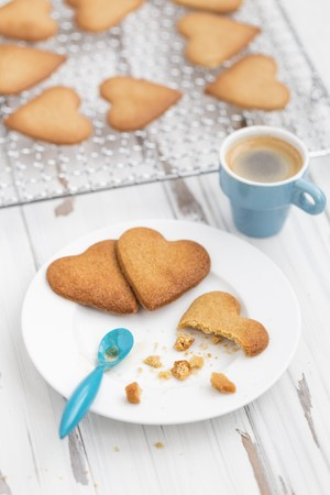 Cooling rack stacked with a grid of heart shaped biscuits on an aged white background with espresso and broken biscuits on a white plate with a blue espresso spoon