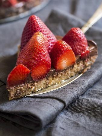 Slice of gluten free chocolate tart served with fresh strawberries