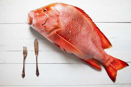 A fresh whole red snapper with a knife and fork