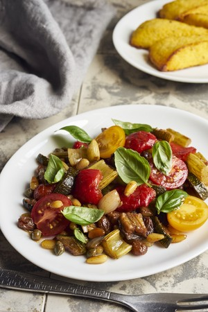 Caponata with peppers and cherry tomatoes served with polenta slices LANG_EVOIMAGES