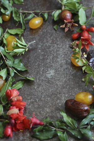 Still life with dates, candied fruit and pomegranate branches