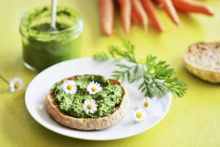 Pesto of carrot leaves as bread spread, decorated with daisies LANG_EVOIMAGES