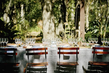 dining table and chairs: A table laid under trees