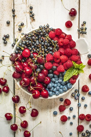 Cherries, blueberries, blackcurrants and raspberries in a bowl