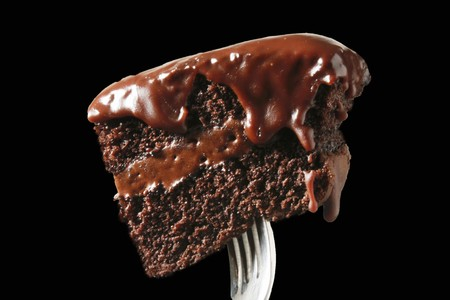 coatings: Large bite of chocolate cake with dripping frosting