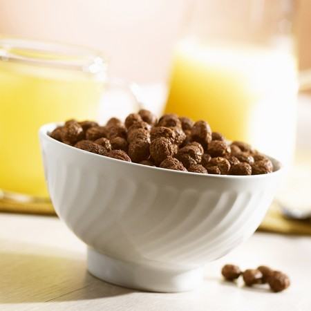 A bowl of cereal chocolate balls and orange juice