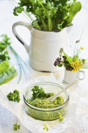 Pesto made from various herbs in the glass, in the background jug with herb bundle
