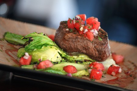Filet mignon with tomato cubes on leaf vegetables