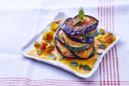 A ratatouille tower with pepper sauce