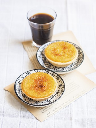 Two Portuguese orange tarts and black coffee