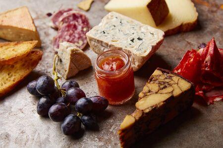 produits alimentaires: Un plateau d'apéritif avec différents types de fromage, salami, raisins et pain