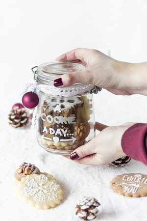 Hands holding a glass jar with decorated Christmas cookies