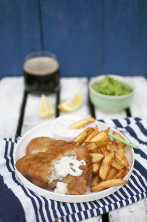 coatings: Fish and chips, served with mashed green peas, pieces of lemon tartare sauce and dark beer