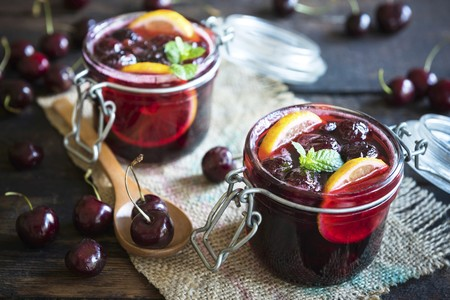 Jam with black cherries and lemon slices in flip-top jars