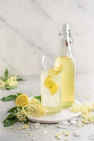 Homemade elderflower cordial in a glass with fresh lemon and ice