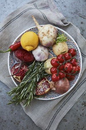 Fresh vegetables, fruits and herbs on a plate (top view)