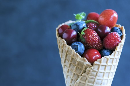 Fresh berries and cherries in an ice cream cone LANG_EVOIMAGES