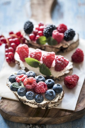 Berry and cream cheese bruschetta on a wooden board LANG_EVOIMAGES