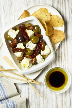 Feta with pickled olives, dried tomatoes, potato chips and olive oil LANG_EVOIMAGES