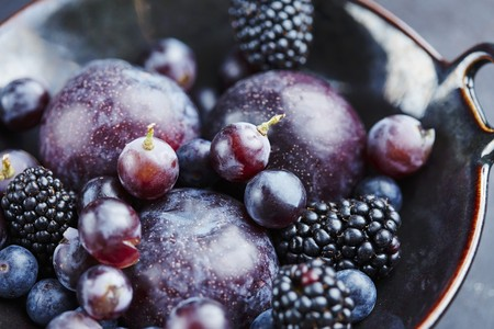 Plums, blackberries, blueberries and grapes in a ceramic bowl