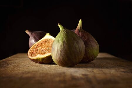 Fresh figs, whole and halved, on a wooden table