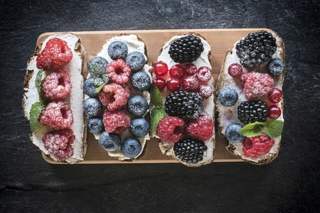 Bruschettas with berries and cream cheese on a wooden board