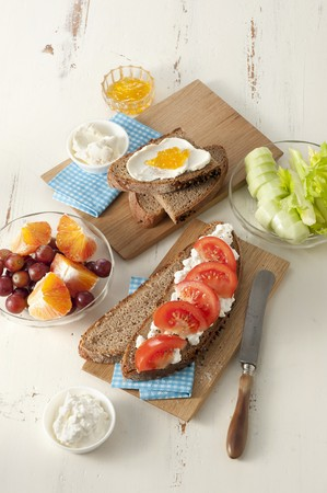 Slices of wholemeal bread topped with fresh cheese and jam, and cottage cheese and tomatoes