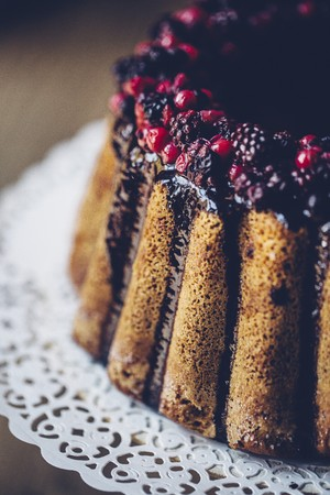 A ring-shaped Bundt cake with berries and chocolate glazing (detail)
