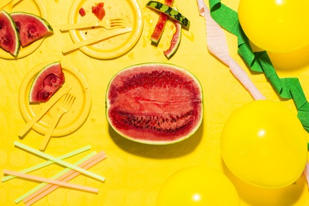 Watermelon cut in half with yellow plates, tablecloth, cutlery and balloons, along with streamers and straws