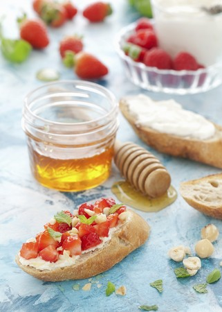 Strawberries, mint and hazelnuts on mascarpone toast with honey