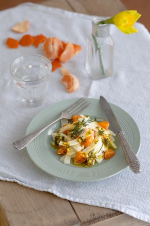 clementines: Salad of sliced fennel, shallot and clementine salad with a zingy dill dressing on a light jade coloured plate with vintage cutlery