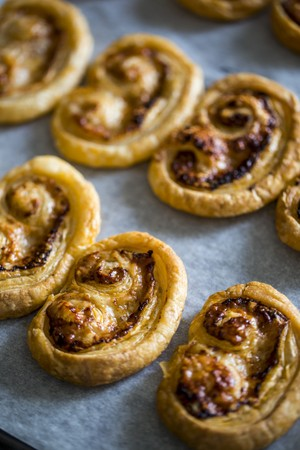 tin: A baking tray with golden cooked comte and pesto palmiers sitting on baking paper. LANG_EVOIMAGES