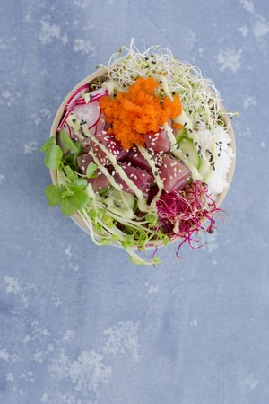 A Poke bowl with tuna, sushi rice, tobiko, radishes, cucumber slices, and sprouts