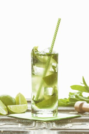 Straight hiball glass with lime mint and soda water alcohol free mojito and a green stripey straw LANG_EVOIMAGES
