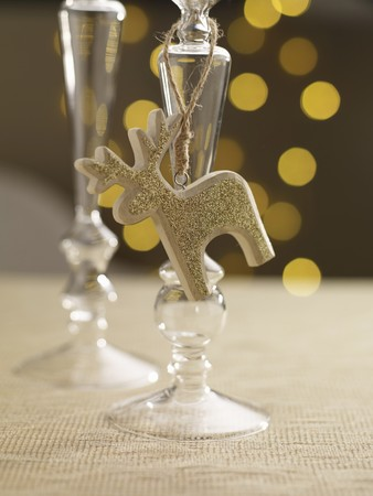 A candlestick holder with a golden reindeer figure on a festively set table LANG_EVOIMAGES