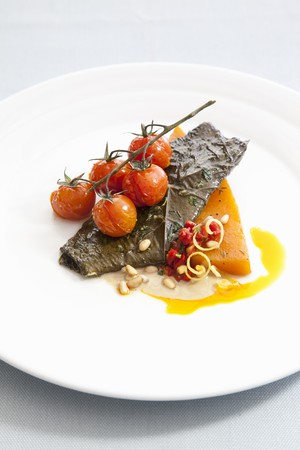 Fillet of Red Drum fish with fried cherry tomatoes and pine nuts