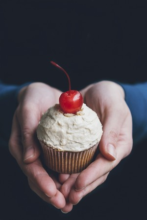 Hands holding a cupcake with peanut frosting and a cocktail cherry LANG_EVOIMAGES