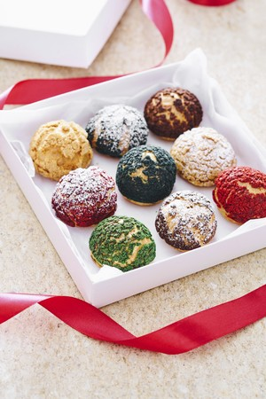 Different-coloured choux pastries in a gift box
