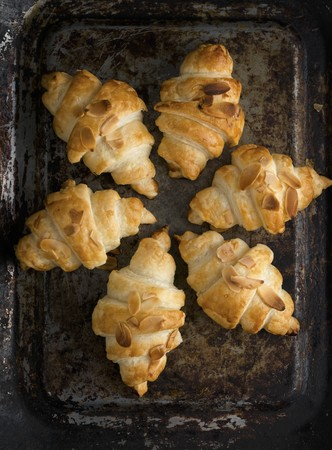 tin: Croissants with almond flakes on a baking sheet