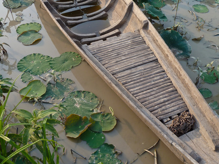 extensively: A small handmade canoe sized wooden canoe style boat next to lily pads in a small pond in Southeast Asia.  Boats are used extensively in Asia for rural and Urban transport.