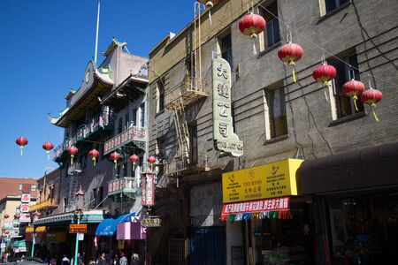 seldom: SAN FRANCISCO, CA - CIRCA MARCH 2015 - Wider view of red Chinese lanterns hanging over a street in Chinatown, San Francisco. English is seldom seen in parts of Chinatown, attesting to an Asian influx.