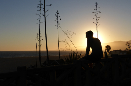 Silhouette of a Person Sitting on Wall During Sunset near Santa Monica Beach, California. Ocean and distant mountains are visible in background during this moment of contemplation.