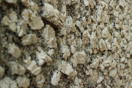 igneous: Close up perspective of igneous boulder surface texture, with camera at surface level looking across the surface wider. Igneous rocks like these, found along the Thailand-Burma border are of volcanic origin, and can result in a formation with varied geolo