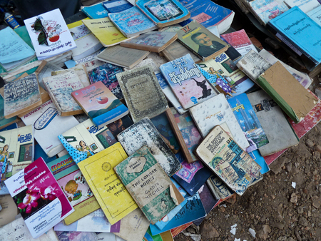 free enterprise: View of used and second hand books on a sidewalk booksellers table in Yangon, Myanmar.  Titles range from English to Myanmar and beyond, in varying conditions.