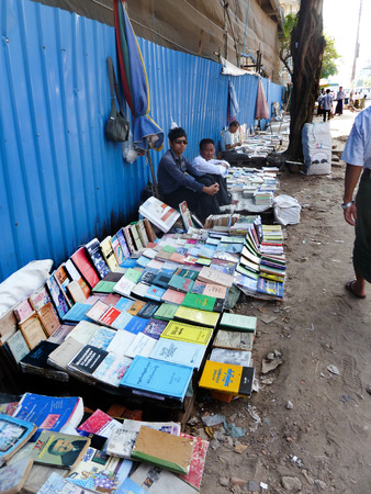 View of a low, makeshift table used by sidewalk booksellers in Yangon, Myanmar to sell used and second hand books. The literary community in Myanmar is surprisingly robust considering the country had been closed for decades.