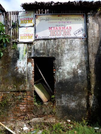 attest: Weatherbeaten Concrete and Brick Building in Burma Myanmar. Defunct walls and aging signs attest to the effects of the incessant tropical climate on brick, wood, and concrete alike.