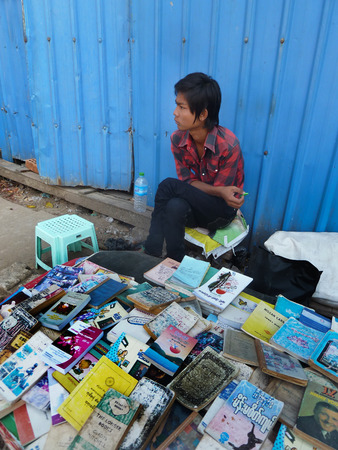 closed community: View of a youthful sidewalk bookseller at his table in Yangon, Myanmar where he sells used and second hand books along the roadside. The literary community in Myanmar is surprisingly robust considering the country had been closed for decades. Editorial
